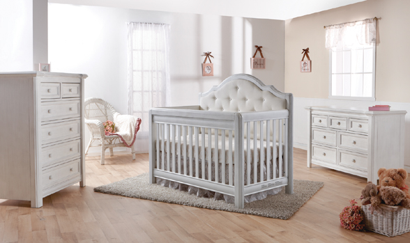 The <b>2200 Cristallo Forever Crib</b> in Vintage White with a <b>fabric upholstered panel headboard</b>. <br>The Cristallo Forever Crib is an enchanting blend of classic lines paired with sweet touches of sophisticated luxury.  The strong, clean design of this crib is highlighted by the layered moldings that frame both the front and the headpiece.  These beautifully rounded layers provide texture and a nod to the elegance of classical architecture.  Set in the headpiece of the crib is a sumptuously tufted panel. Providing a distinct sense of playful beauty, this sweetly textured cushion is designed with both style and use in mind.
