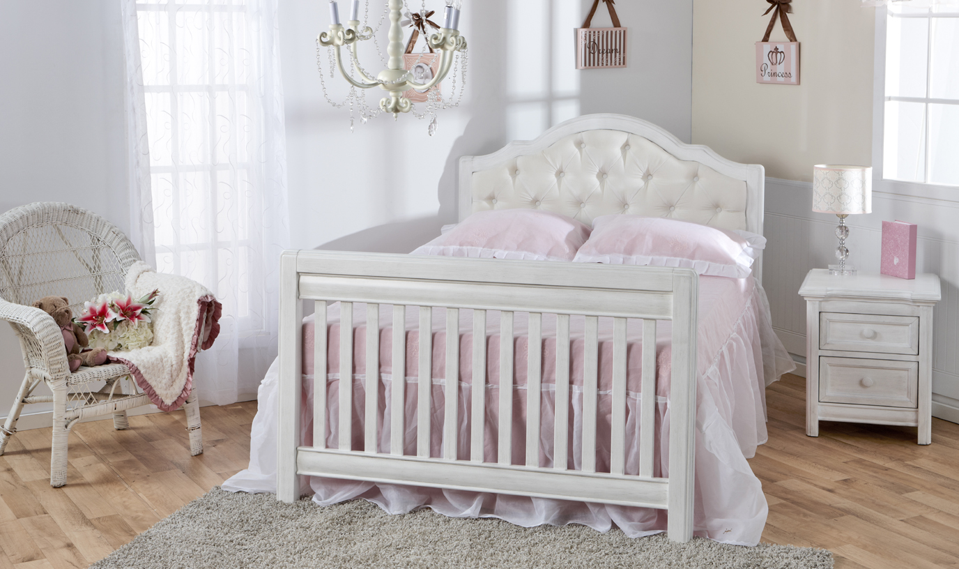 The <b>Cristallo Collection</b>. <br>An example of elegance and distinction, featuring an upholstered headboard convertible crib.  <br>Please note that the full-size bed conversion rails are available in both Granite and in Vintage White.