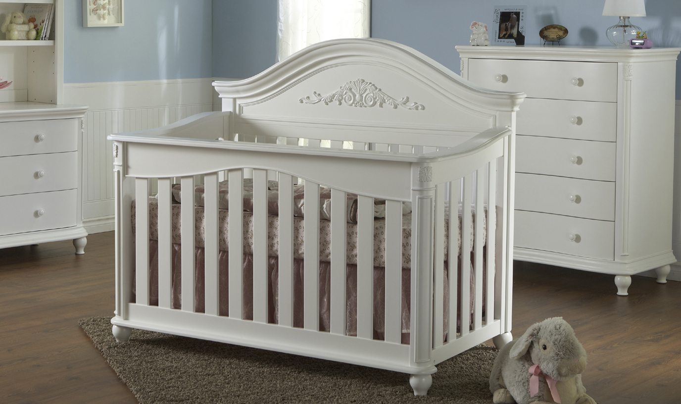 The <b>Gardena Forever Crib </b> in White.<br>The Gardena Forever Crib is a lovely example of the collection's heritage with an intricately carved appliqué placed in the center of the delicately curved headboard.  The carving motif continues throughout the piece with decorative details at the top of each footboard post and a sweetly curved footboard with an inset edge.  The feet of the crib have been designed with a decorative trim that highlights the beauty of the piece.  With all of the attention to details, the Gardena Forever Crib is a beautiful piece of art for your little one's room.